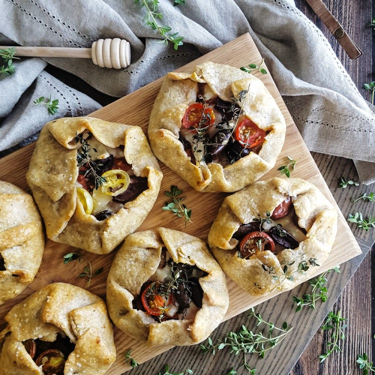 A hearty cornmeal crust wraps up layers of #summer flavor in these rustic Ratatouille Hand Pies. Stacked roasted #eggplant, ripe heirloom #tomato, melty #cheese, and a sprinkling of fresh herbs and briny# olives makes for a travel-ready meal, perfect for any #picnic or #potuck. #handpies #gallette #travel   FeastInThyme.com