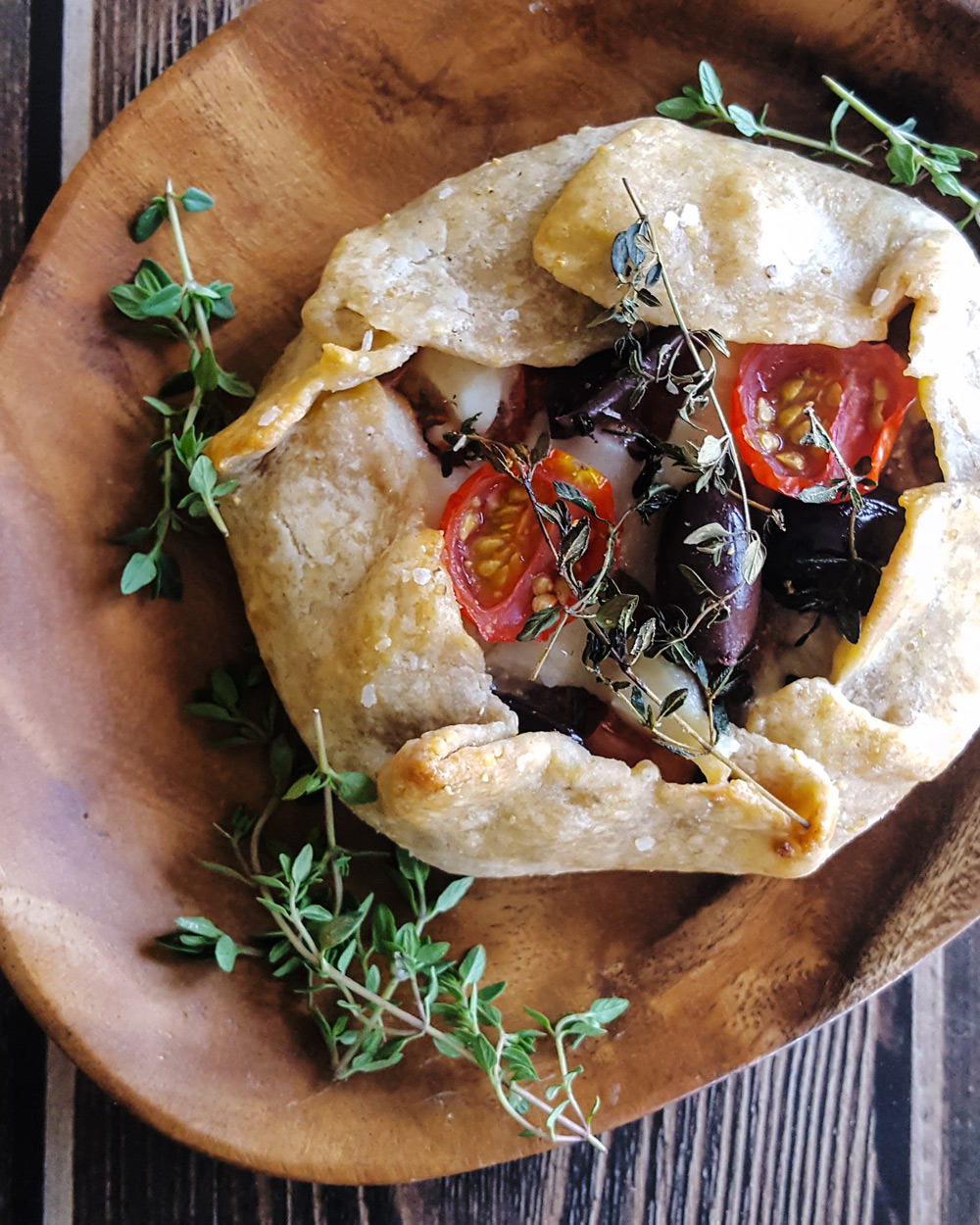 Single Ratatouille Hand Pie with purple olives, red cherry tomatoes, and thyme leaves. | FeastInThyme.com