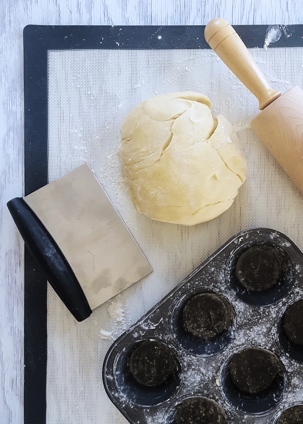 Ball of dough with rolling pin, bench scraper, and floured muffin tin.