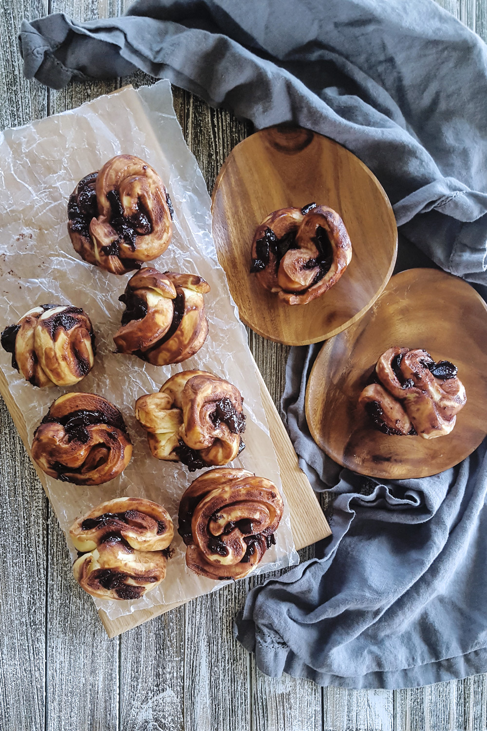 An assortment of Cherry Chocolate Babka Pull Apart Muffins on a wooden tray and two wooden serving plates with a grey napkin.