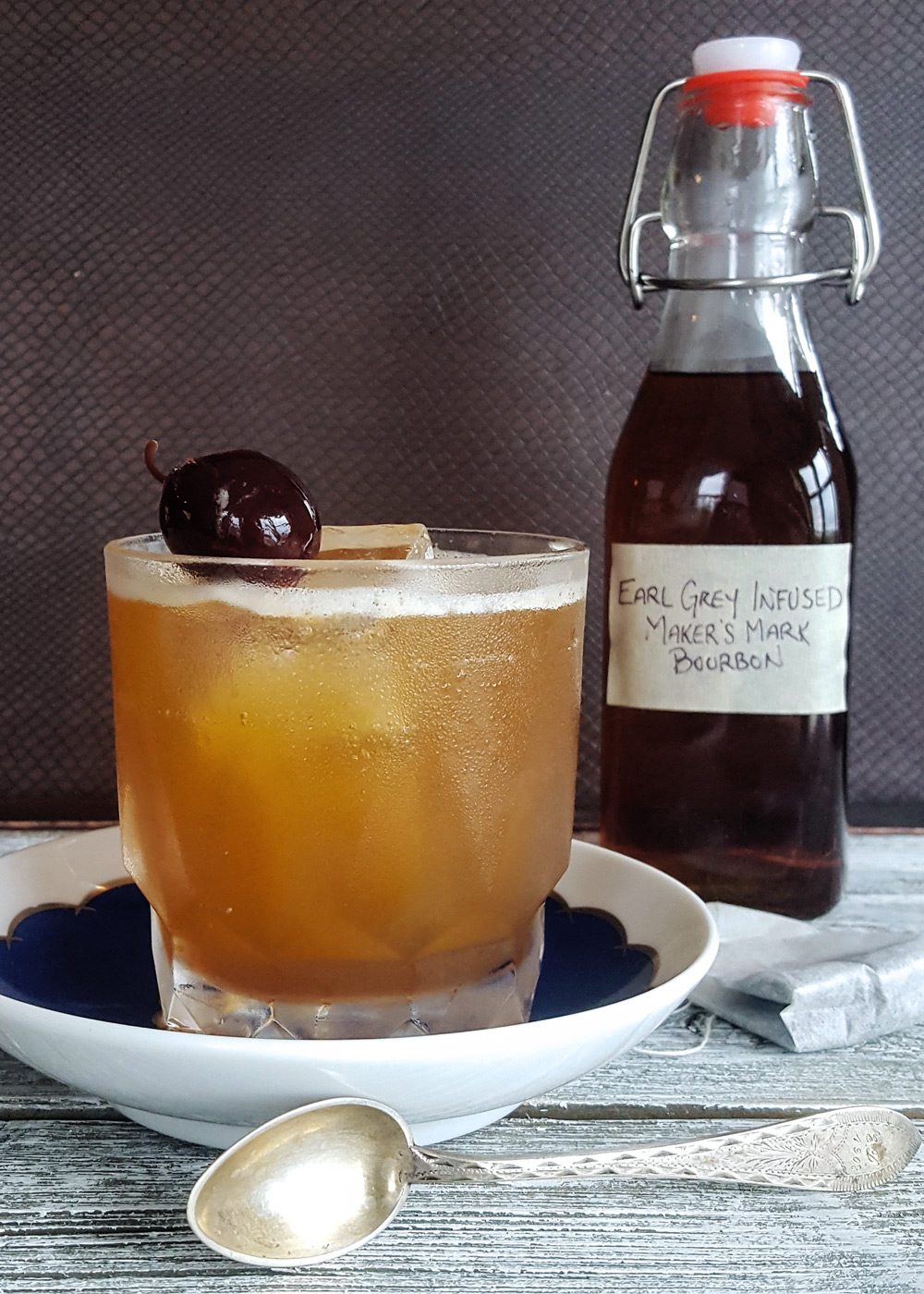 An Earl Grey Manhattan in front of a bottle of tea infused bourbon on a wooden platform.