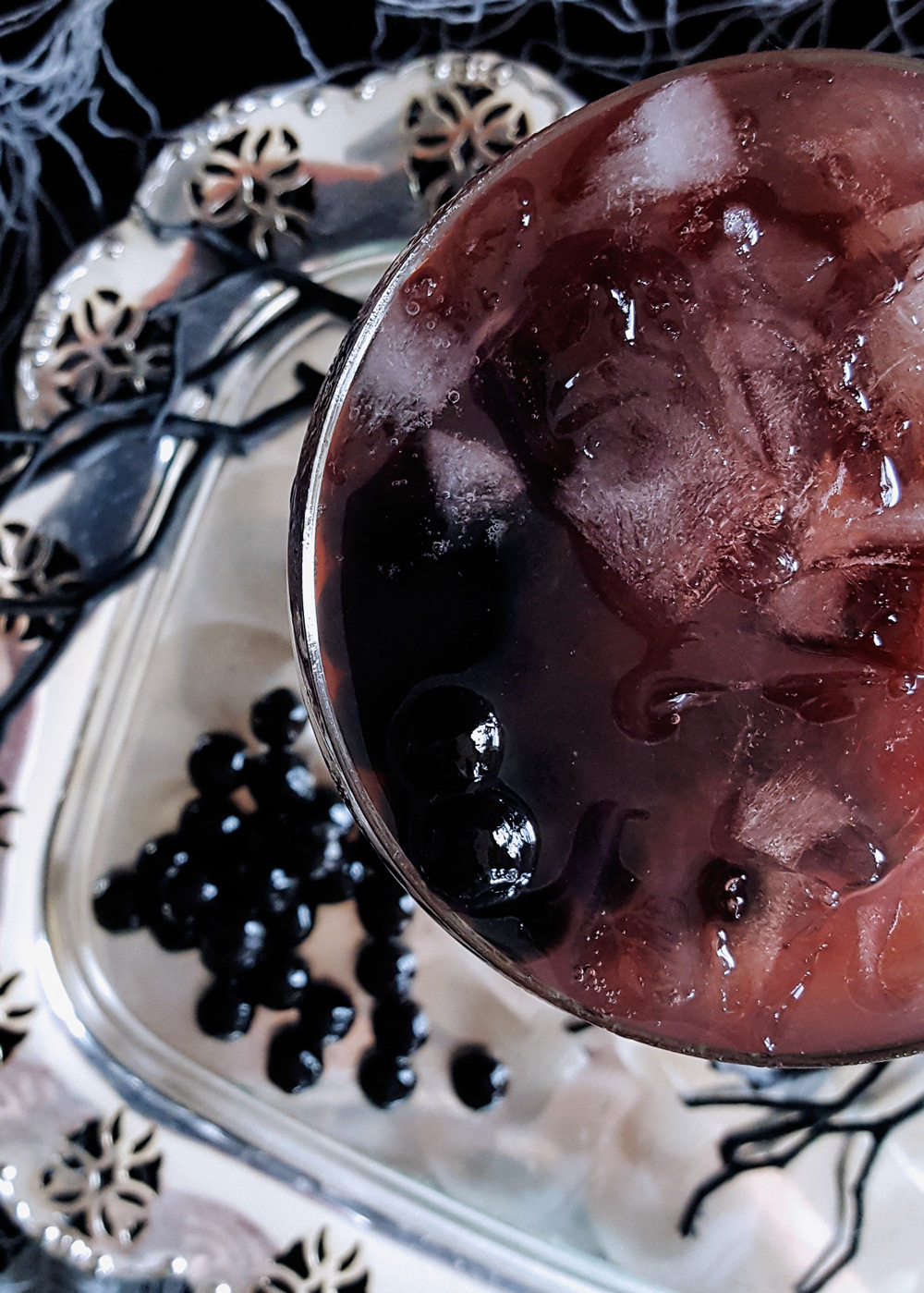 Overhead shot of a coupe glass of bourbon pomegranate punch garnished with black tapioca pearls.