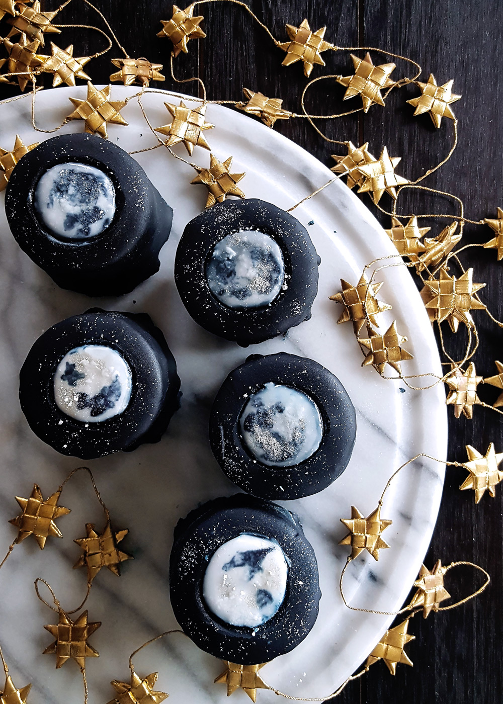 A marble platter full of tiny takes with painted full moons, set on a black table with a golden star garland around them.