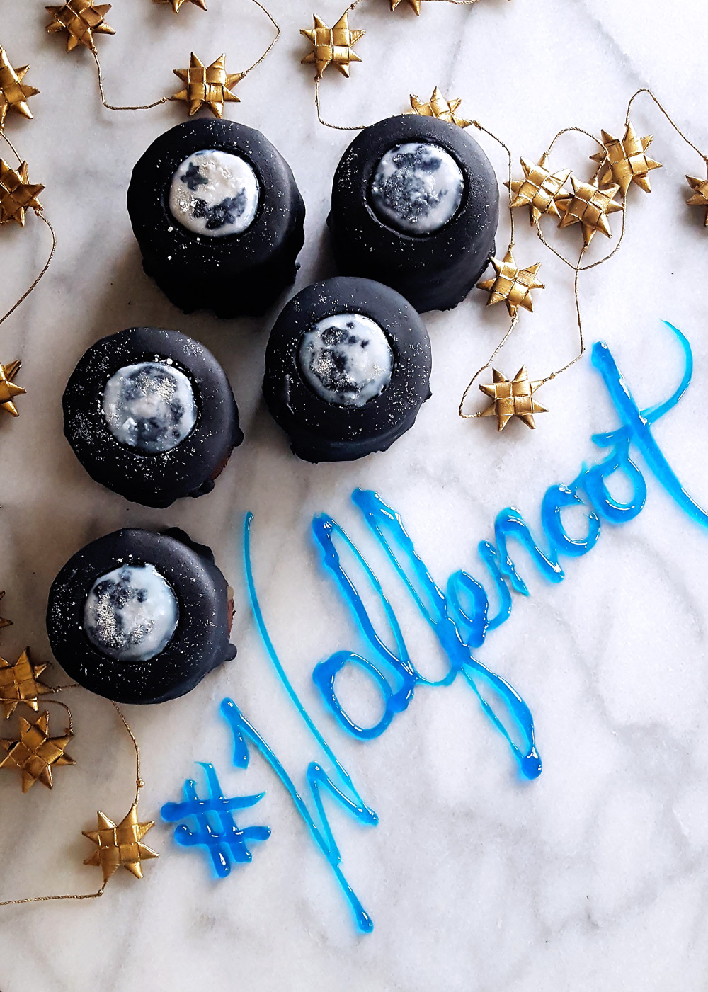 Wolfenoot chocolate layer cakes on a marble slab with the name of the holiday written in icing. FeastInThyme