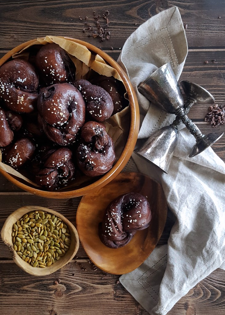 Overhead shot of a bowl of dark ale pretzel knots, with one on a plate and two metal goblets.