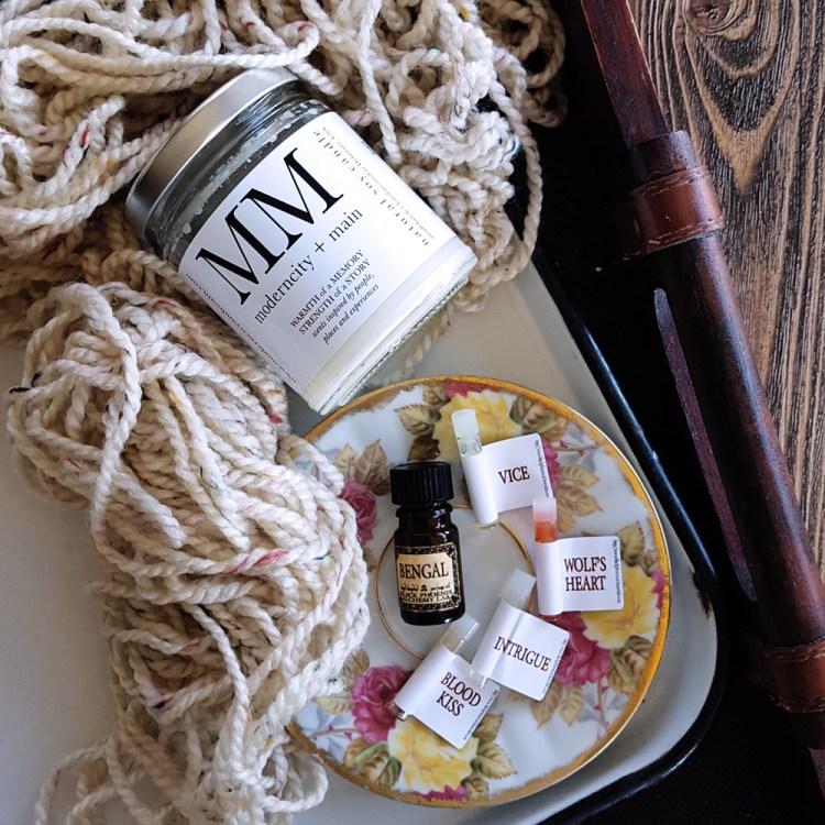 A Modern City & Main Candle alongside bottles of Black Phoenix Alchemy Essential Oils on a white enamel tray. | FeastInThyme.com