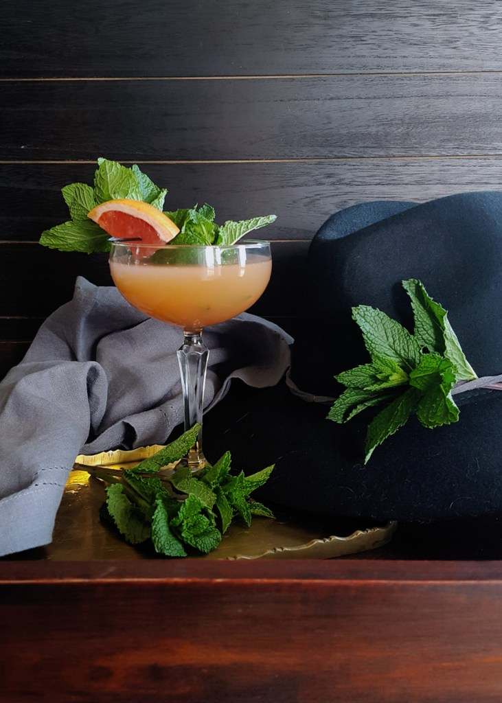 A coupe glass of bourbon grapefruit cocktail pair with a black fedora.