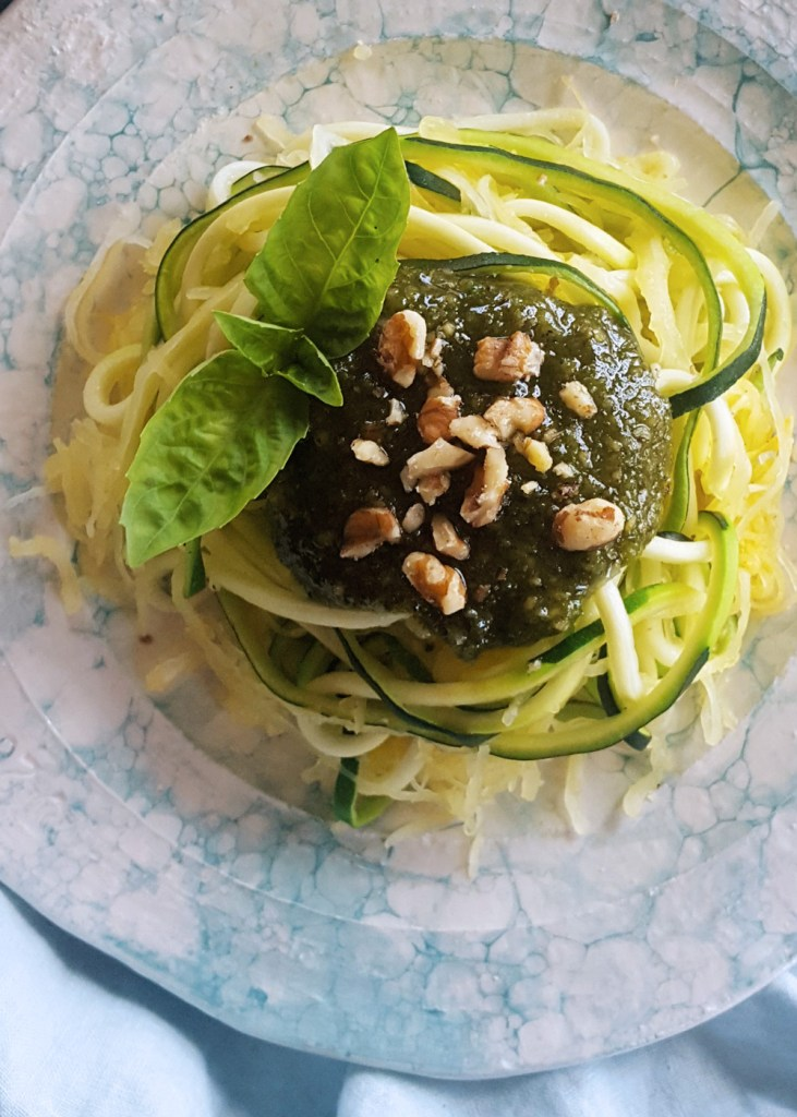 Zucchini noodles and spaghettie squash topped with basil walnut pesto.