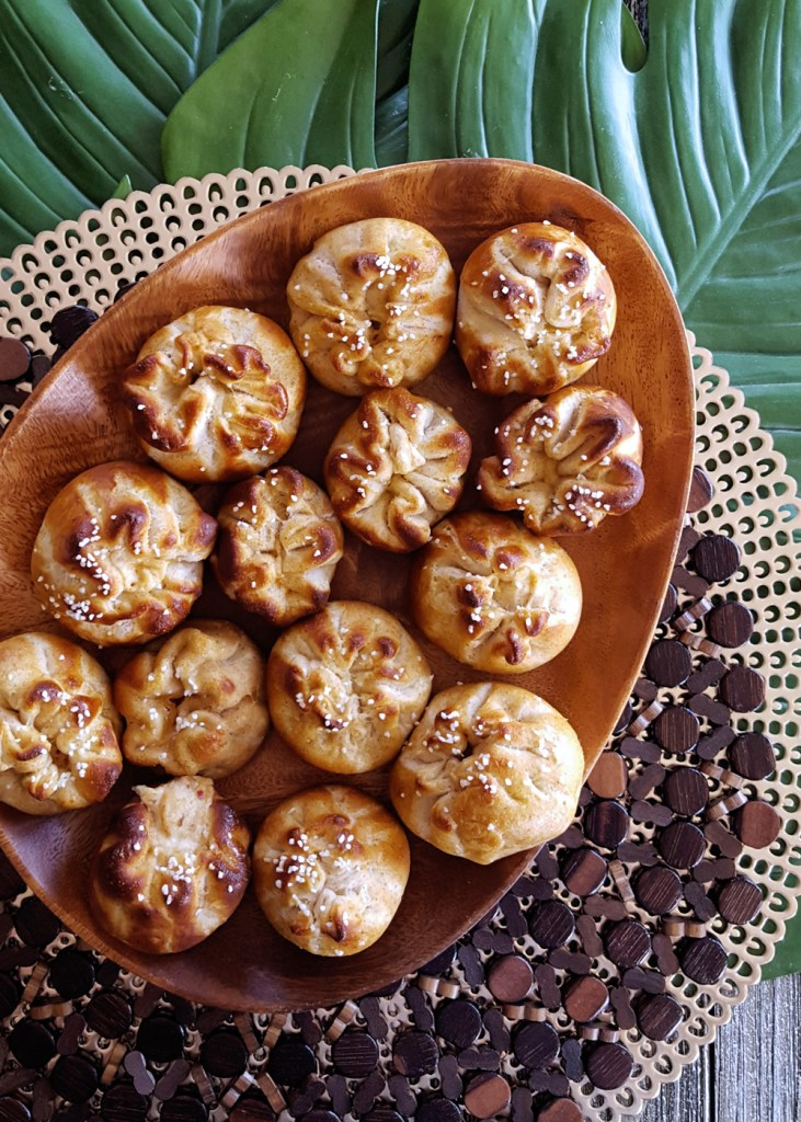 A platter of pleated crab rangoon pretzel buns on layered tropical placemats.