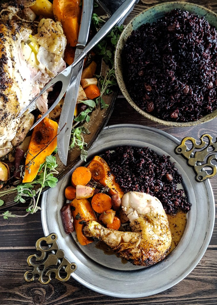 Overhead view of a carved roast chicken and a bowl of black forbidden rice, next to a plate of the same portioned out.
