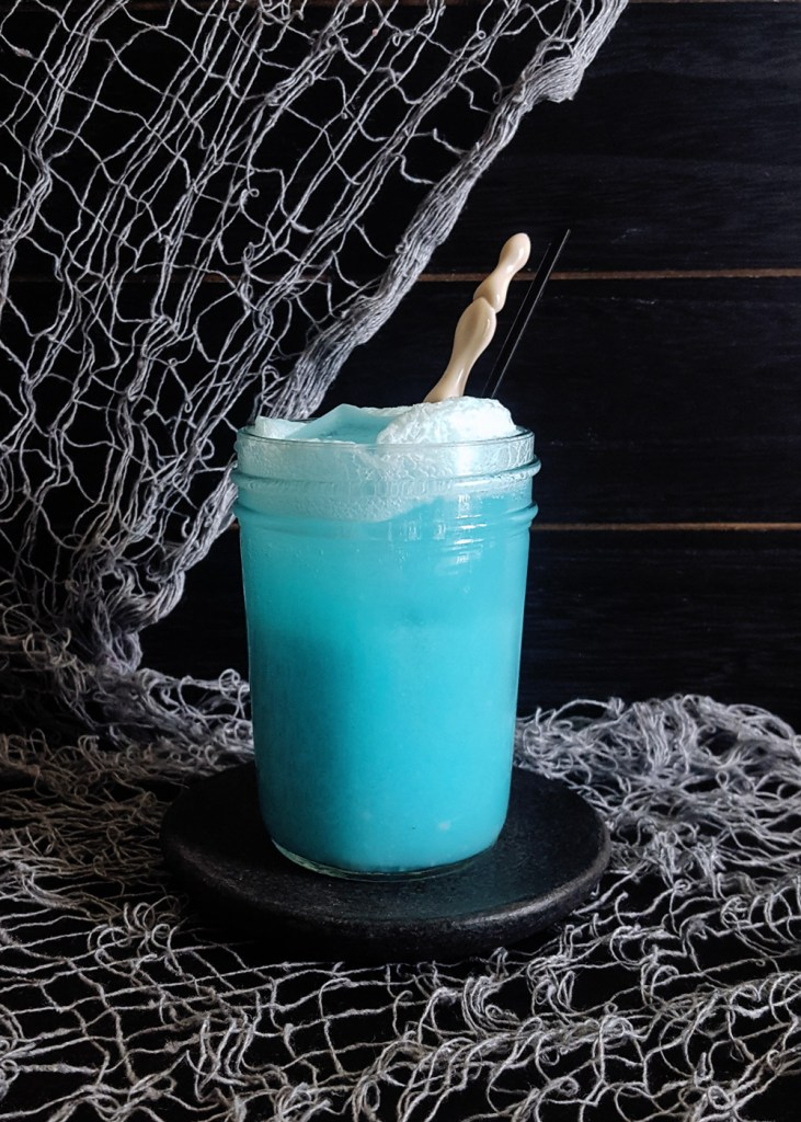 A bright blue gin cocktail with a finger-bone style swizzle stick against a black background.