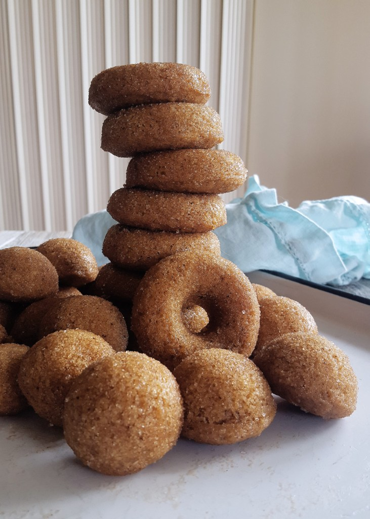 A teetering tower of hard apple ciderc donuts on a white enamel tray.