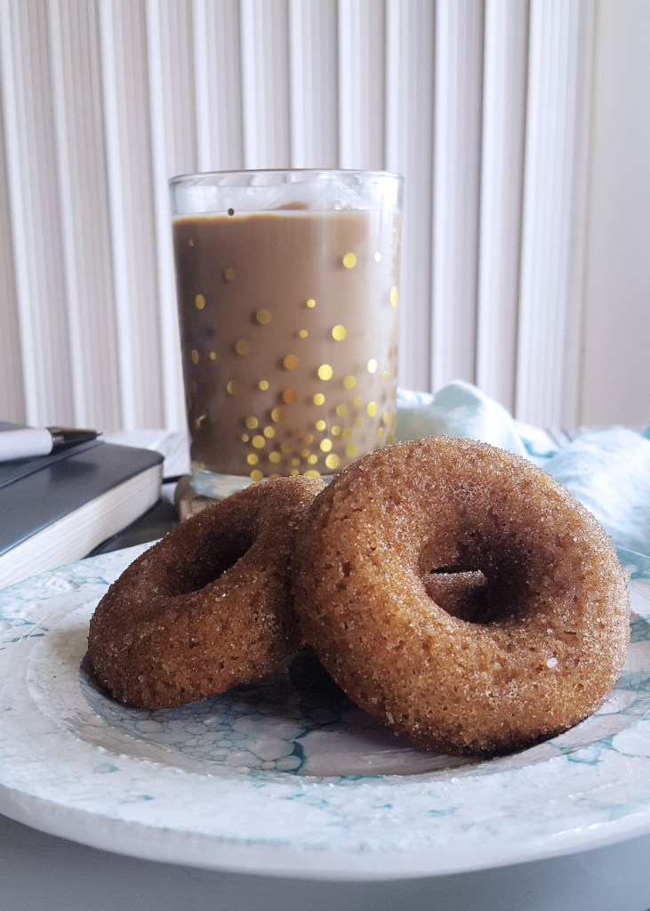 Two hard apple cider donuts with a glass of iced coffee in the background.