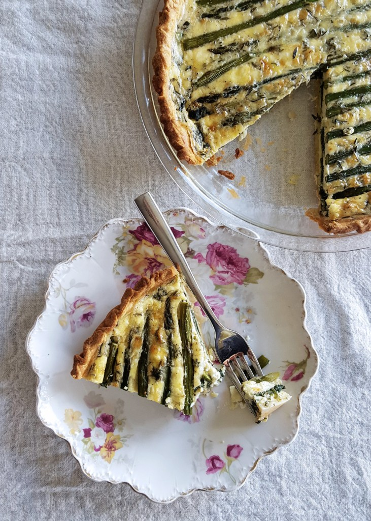 An asparagus goat quiche with a slice removed, and a forkful taken from the slice on a white linen clothe.