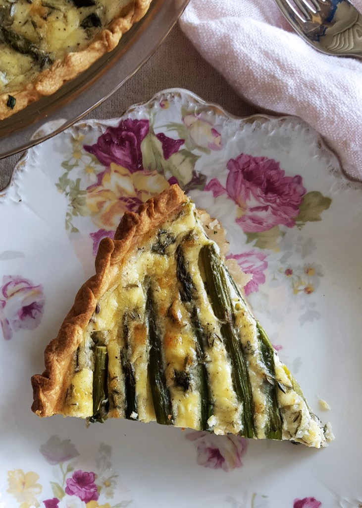 A single slice of asparagus goat cheese quiche on a floral plate.