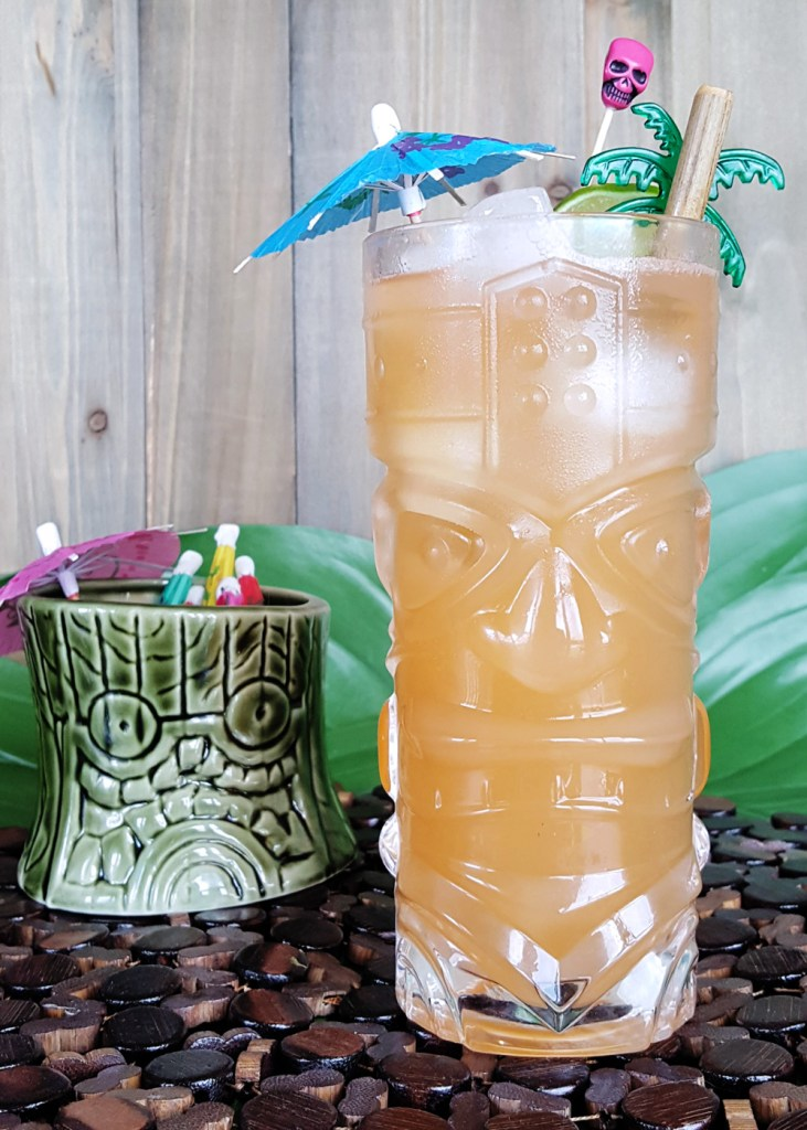 Side by side image of a glass of Zombie Punch and a small tiki mug filled with paper umbrellas.