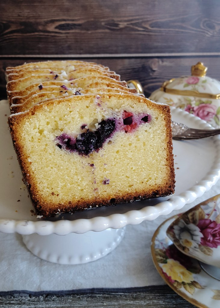 A close-up of a slice of Harken Cake, with raspberries and blueberries at its center.