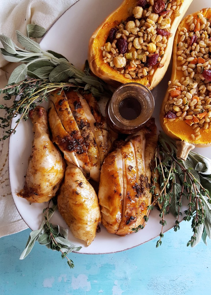 A platter of carved chicken and a side of stuffed butternut squash.