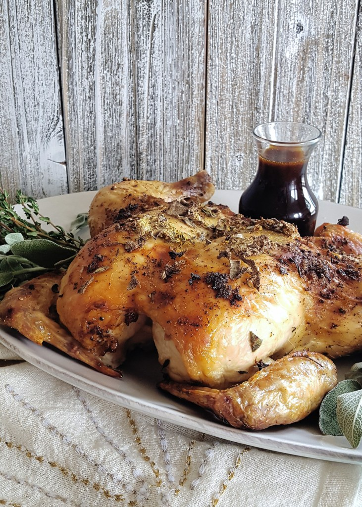 Side view of a whole roasted spachcocked chicken with a carafe of bourbon brown sugar glaze.