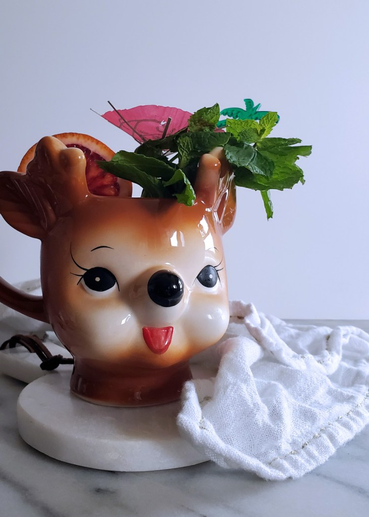 Smiling reindeer mug full of tropical gingerbread cocktail with a white background.