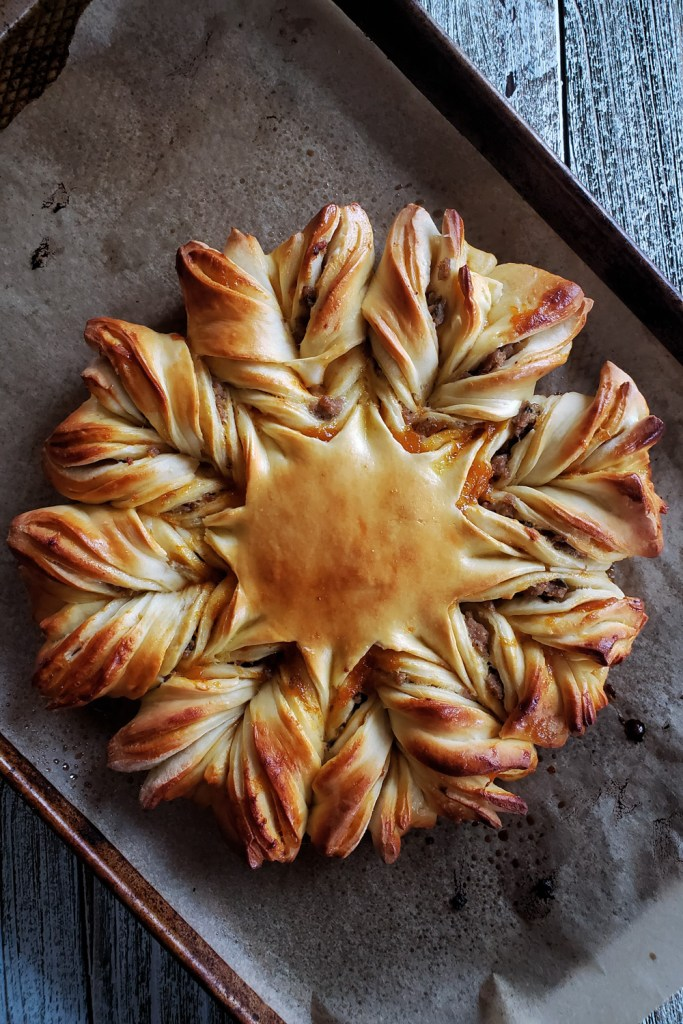 A circular pull apart bread with twisted points, stuffed with apricot jam and sausage on a baking sheet.