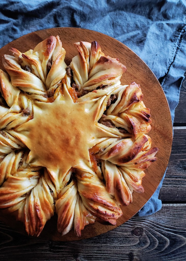 The pull apart bread star on a wooden stand with a grey clothe in the background.