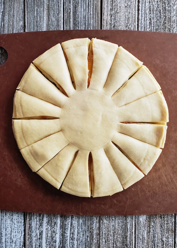 A prep photo of the circles of unbaked dough layered, stuffed, and segmented into 16 parts.