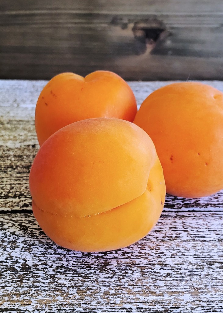 Close-up of three fresh apricots