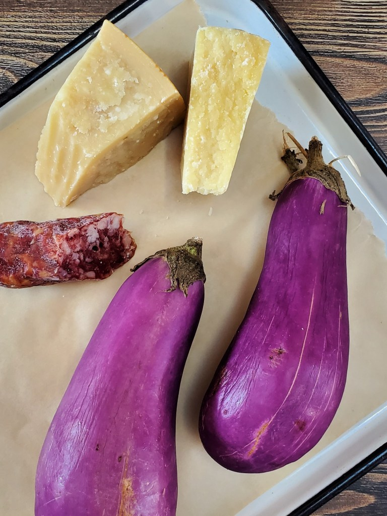 A tray of fresh ingredients, including two hunks of hard cheese, a log of soppressata, and two light purple eggplants.