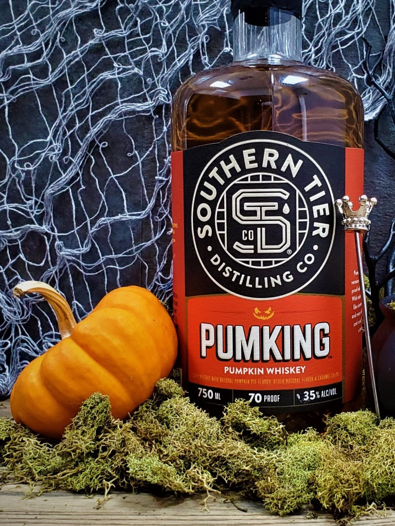 A bottle of Southern Tier Pumking Whiskey with a crown-topped cocktail pick and small orange pumpkin.