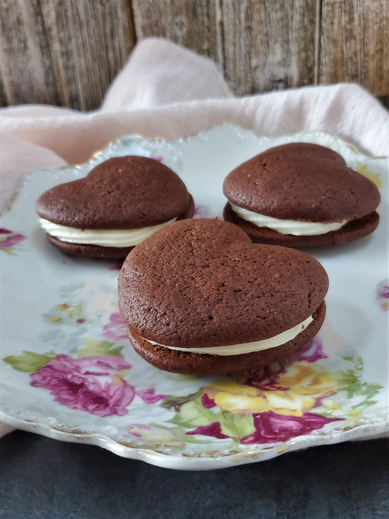 Three red velvet whoopie pies on a floral tea plate.