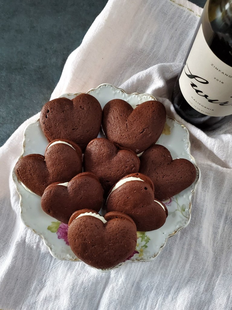 Plate of heart-shaped red velvet whoopie pies next to a bottle of red wine.
