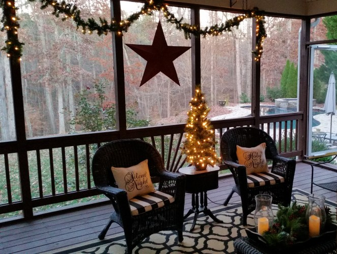 Screened porch with lighted tree, garland and large red metal star.