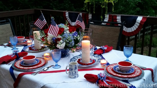 Pillar candles in hurricanes and votive candles light up Old-Fashioned 4th of July Tablescape
