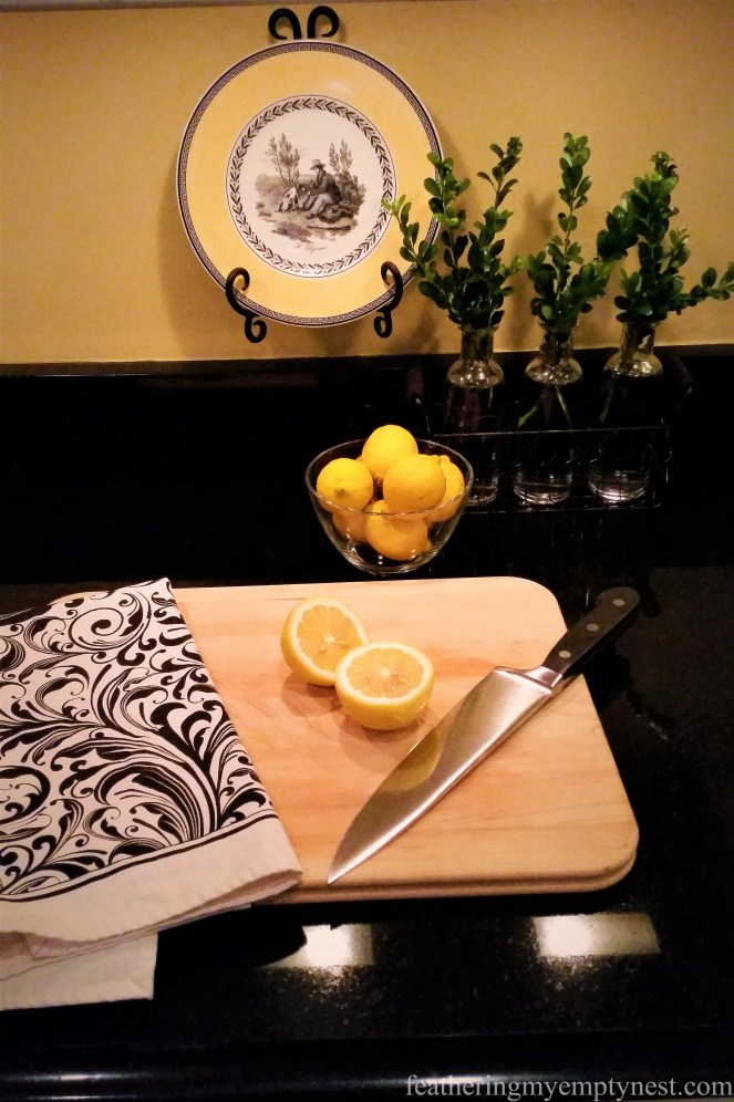 Boxwood sprigs, lemons, and decorative plate serve as outlet camouflage -Inexpensive Kitchen Updates And Camouflage