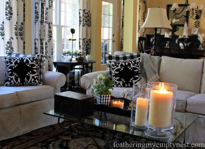 Strong black accents in a family room with neutral linen slipcovered sofa and loveseat-- Why My Family Room Decor Is Always A Work In Progress