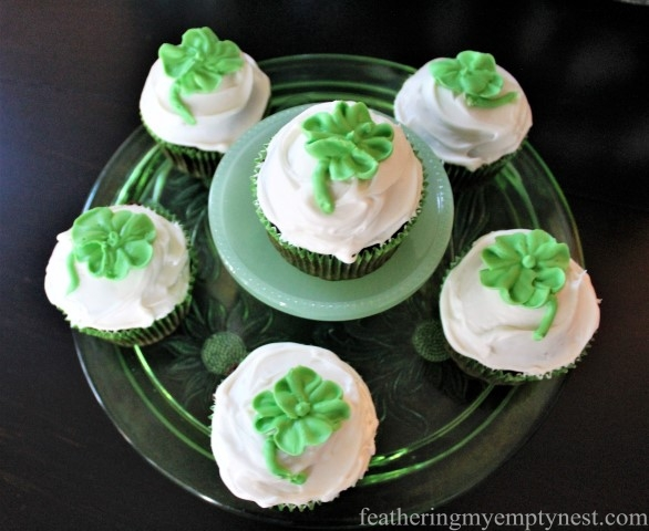 Green glass cake plates display a dozen lucky four-leaf Shamrock cupcakes --St. Patrick's Day Irish Cream Shamrock Cupcakes