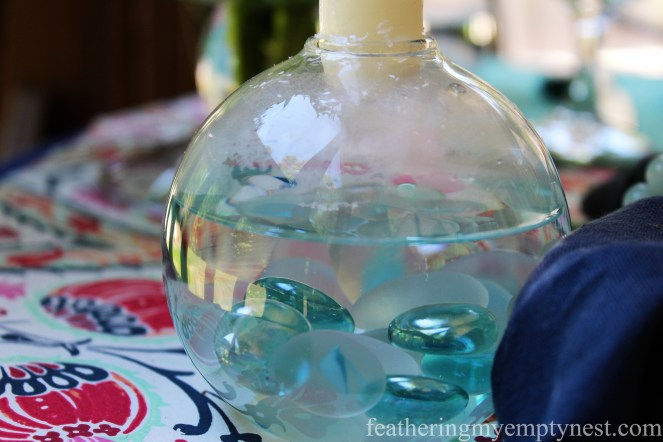 Water and sea glass candleholders on An Impromptu Outdoor Dining Table For Two
