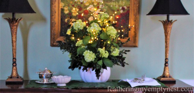 Buffet arrangement of hydrangeas, greenery, and lighted pussy willow branches in a pumpkin tureen --A Nature-Inspired Elegant Thanksgiving Tablescape