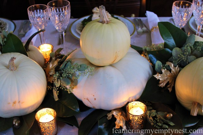 White pumpkins, magnolia leaves, seeded eucalyptus, and golden votives, acorns, and leaves make a simple but stunning centerpiece --A Nature-Inspired Elegant Thanksgiving Tablescape