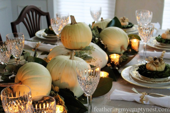 White pumpkins, magnolia leaves, and gold touches make a simple but beautiful table --A Nature-Inspired Elegant Thanksgiving Tablescape