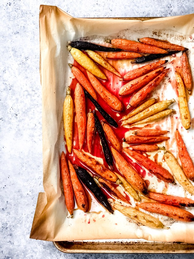 Brown Butter Roasted Rainbow Carrots with Blood Orange juice arranged on on a baking sheet.