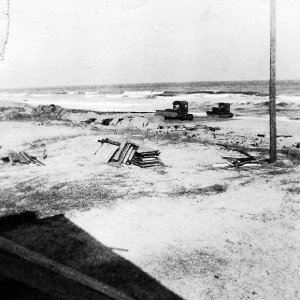 Bulldozers pushing sand to form a beach hill. The power pole was behind beach hill prior to Hazel.
