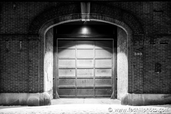 Fine art black and white photograph of footprints in snow past a fire station at night in Baltimore City, Maryland.