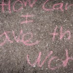 'How can I save the world' written in child-like style with chalk on sidewalk in Baltimore, Maryland.
