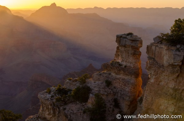 Fine art photo of rays of sunlight shining through mist and canyon rim at sunrise in Grand Canyon National Park, Arizona.