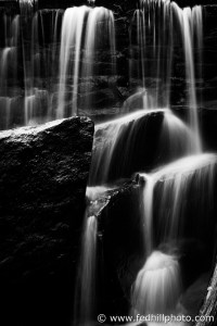 Black and white fine art photo of waterfall over stone dam, splashing on rocks.