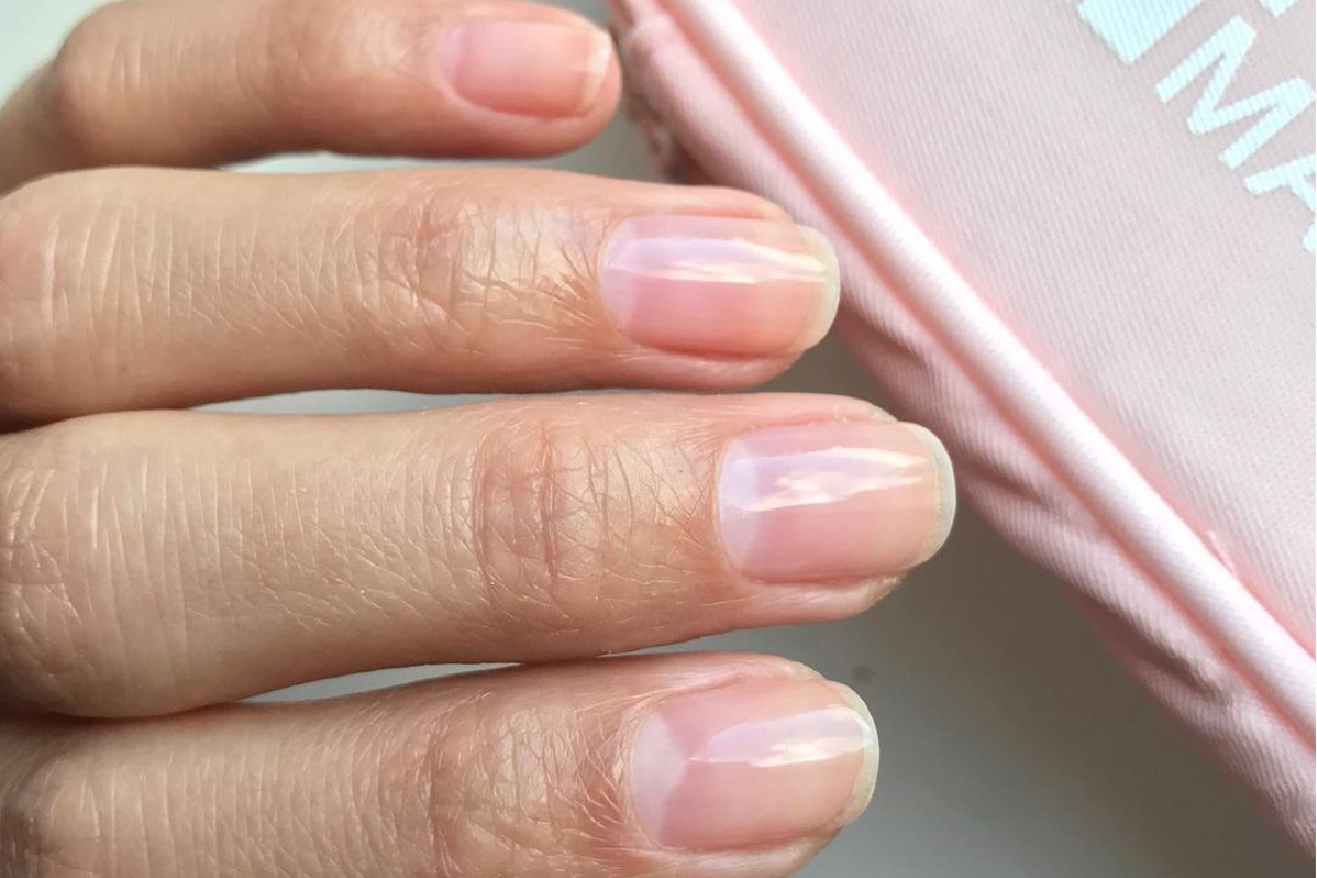 A hand is displaying the Gelie-Cure Foundation manicure on her fingernails, with the Gelie-Cure System pink bag visible in the corner.