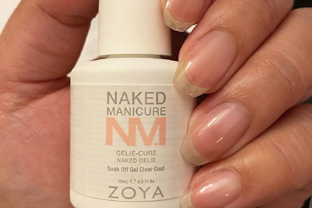 A hand is holding the ZOYA Naked Manicure Naked Gelie, with the Gelie-Cure Foundation Manicure on their bare fingernails.