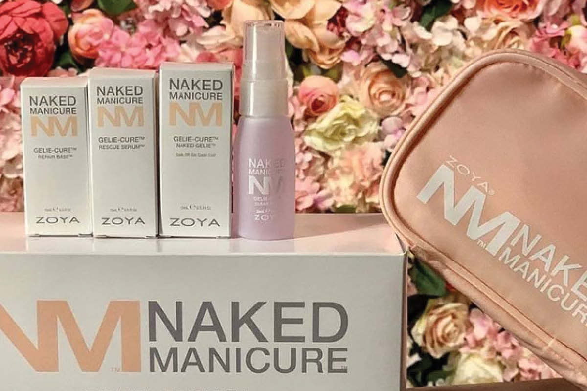 ZOYA Naked Manicure's Rescue Serum, Repair Base, Naked Gelie, and Clear Shine Spray are shown in their boxes on top of a Naked Manicure box. The Gelie-Cure System bag is propped against the box display with a flowered background behind it.
